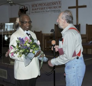 VFP President Jay Wenk presents flowers and a card to pastor Rev. Dr. G. Modele Clarke