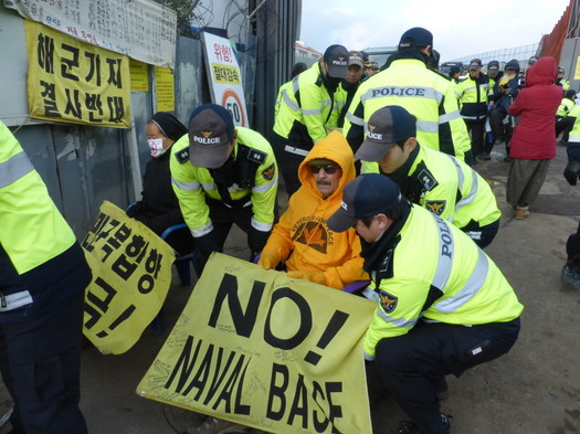 Veterans For Peace delegation organizer Tarak Kauff is set down at the side of the base entrance by South Korean police. Photo by ELLEN DAVIDSON